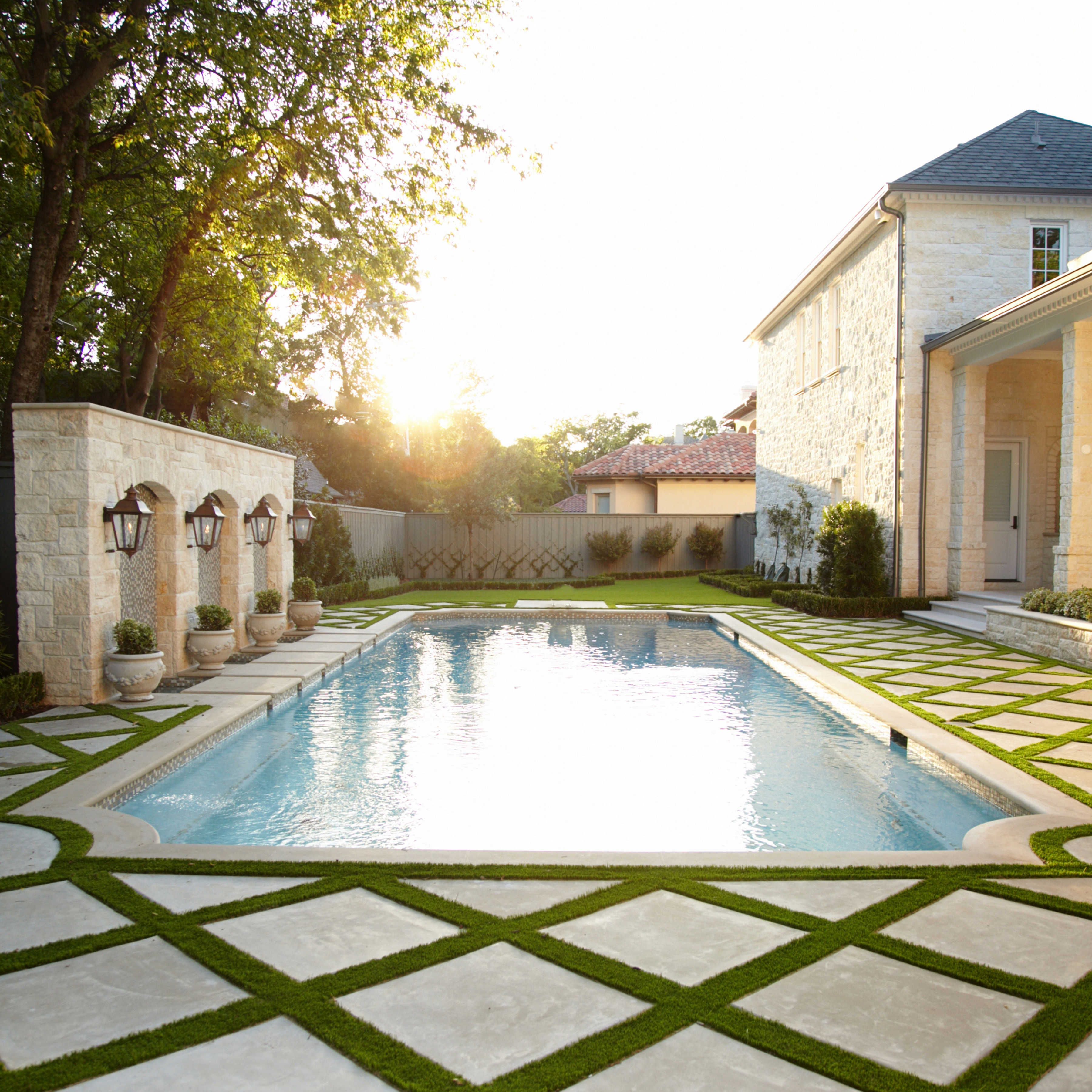 This Parisian influenced garden features a swimming pool, gas lanterns, trimmed hedges, and custom paving integrated with synthetic grass. Along the back of the pool, a nine foot tall focal wall showcases water curtains, glass mosaic tile, gas lanterns, and decorative pottery. Inside the covered patio, an outdoor kitchen, fireplace, and multiple seating areas were added for entertaining.