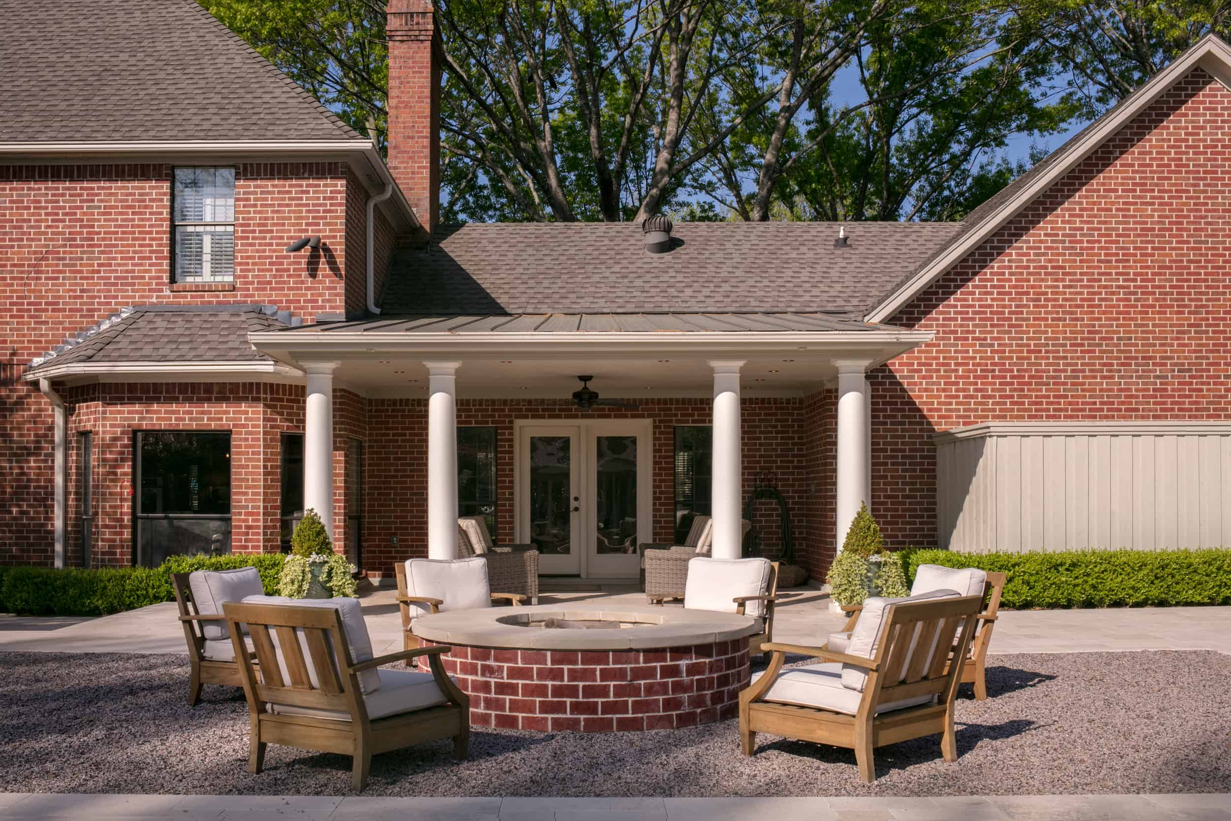Brick firepit with limestone coping and teak restoration hardware chairs in gravel area