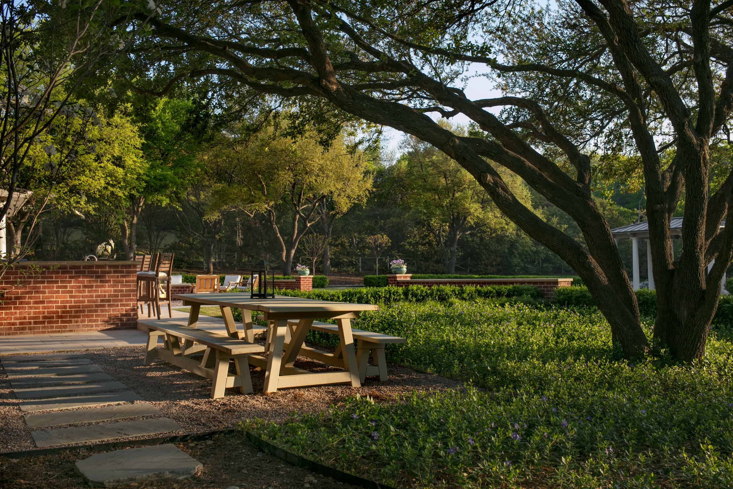 The outdoor dining space is shaded by a mature live-oak (Quercus virginiana). The teak table sits in a bed of gravel surrounding by periwinkle vines (vinca minor).