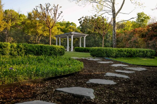 A silvermist flagstone pathway extends from the main limestone terrace through the outdoor kitchen, into the kids playground and out to the great lawn.