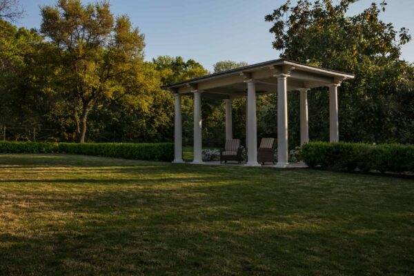A colonial style pavilion overlooks the Great Lawn. Boxwood hedges surround the great lawn and a gravel pathway allows one to navigate the outside of the hedge.