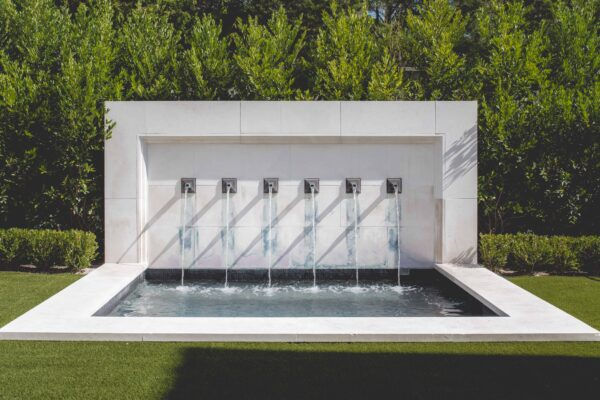 This beautiful carved limestone fountain doubles as a heated spa. The unique Zinc-coated copper water spouts were designed and furnished by Matthew Murrey Design.