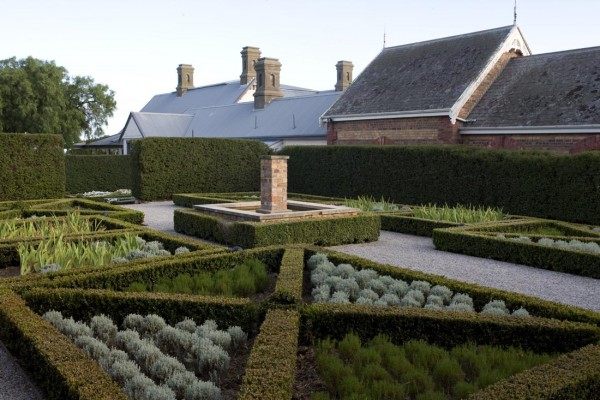 Organized vegetable garden surrounded by boxwoods. Designed by Paul Bangay.